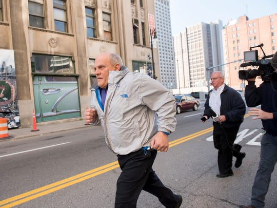 Chesterfield Township Supervisor Michael Lovelock runs from reporters outside the federal courthouse in downtown Detroit on November 17, 2016.