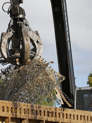 A crane claw is operated at a scrap yard.