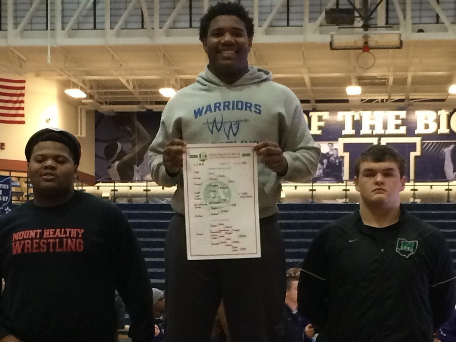 Winton Woods' Jerron Cage holds up the Division I sectional bracket he won last season at 285 pounds.