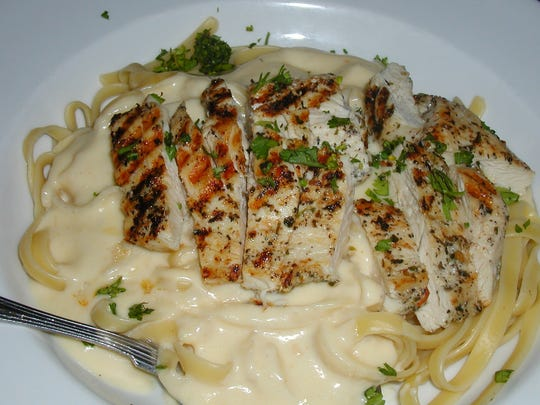 Fettuccini alfredo topped with breaded chicken breast is a popular dish.