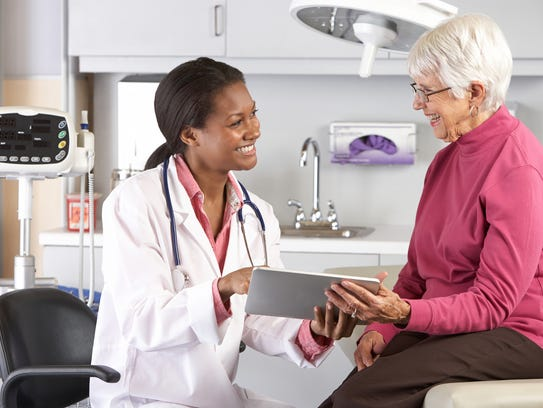 Doctor discussing records with senior female patient.
