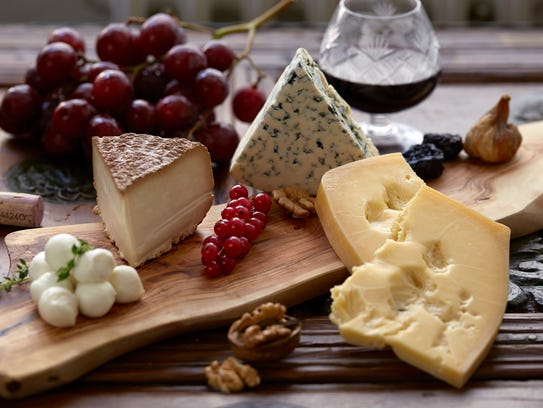 A cheese plate featuring several cheeses, nuts, grapes