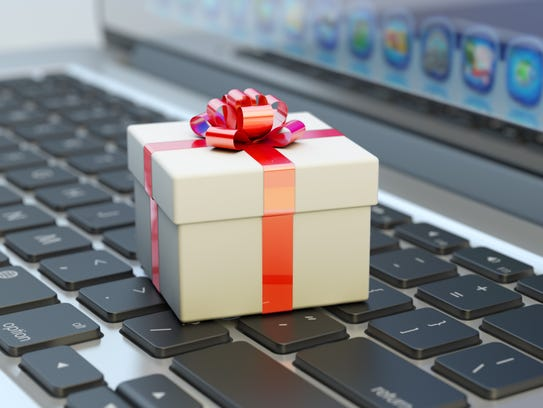 White gift box with red ribbon bow on computer laptop