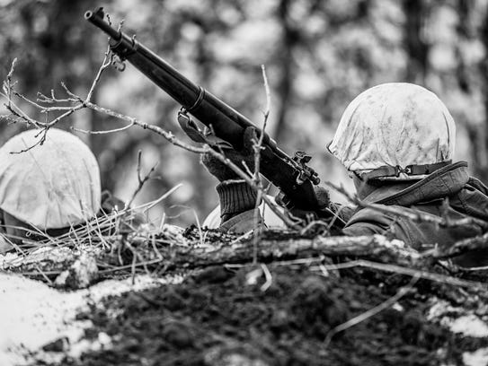 United States Army WWII soldiers in a snowy forest