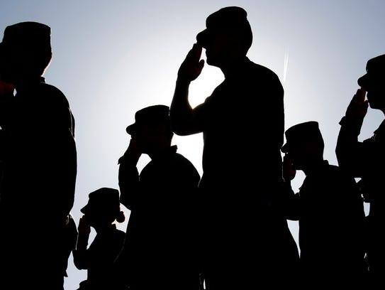 Several soldiers salute the flag at sunset during a