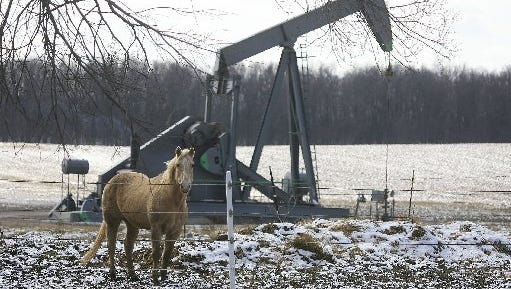 A horse shares  space with an oil well at the intersection of Tipton Highway and Moore Road in Adrian.