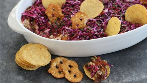 This Jan. 26, 2015 photo shows the Seattle super seven dip, made with teriyaki-seasoned Dungeness crabmeat, creamy cheese, caramelized onions, smoked mussels, purple cabbage slaw and blackberry vinaigrette, in Concord, N.H.