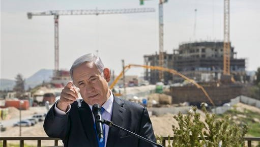 Israeli Prime Minister Benjamin Netanyahu talks as he visits a construction site in  Har Homa, east Jerusalem, Monday March 16, 2015, a day ahead of legislative elections. Netanyahu is seeking his fourth term as prime minister. (AP Photo/Olivier Fitoussi)