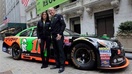 Race car driver Danica Patrick and GoDaddy CEO Blake Irving pose for photos in front of the New York Stock Exchange.