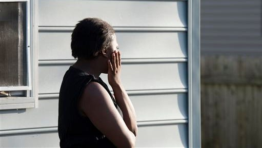 A woman looks away as bodies are removed from a house, where police say seven children and one adult have been found dead Monday, April 6, 2015, in Princess Anne, Md. Police were sent to the home Monday after being contacted by a concerned co-worker of the adult.