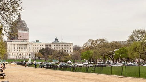 A small helicopter lands at right on the West Lawn of the Capitol in Washington, Wednesday, April 15, 2015. Police arrested a man who steered his tiny, one-person helicopter, astonishing spring tourists and prompting a temporary lockdown of the Capitol Visitor Center.