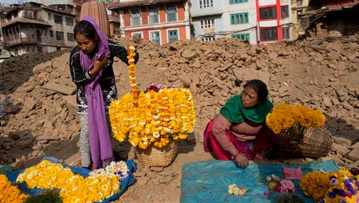 Nepalese flower vendors wait for customers at the Basantapur Durbar Square, damaged in the April 25 earthquake in Kathmandu, Nepal, Tuesday, May 5, 2015. Nepal is one of the world's poorest nations, and its economy, largely based on tourism, has been crippled by the earthquake, which left thousands dead. (AP Photo/Bernat Amangue)
