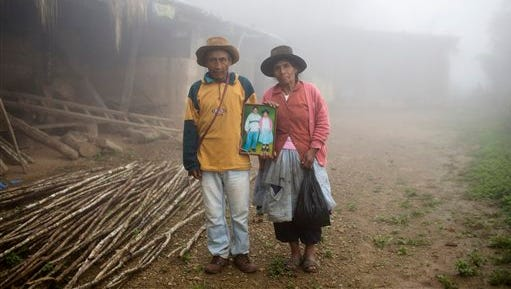 In this March 15, 2015 photo, Julio and Rufina Galvez pose for a picture holding a portrait of their late son Yuri, outside their home, in La Mar province of Ayacucho, Peru. The 25-year-old university student had gotten his father's permission to haul coca in a backpack to pay for his agronomy studies, his mother said. Yuri was found face-up on a mountain trail, with bullet wounds to his head, stomach and arm, in a March 2013 cocaine smuggling trip.  (AP Photo/Rodrigo Abd)
