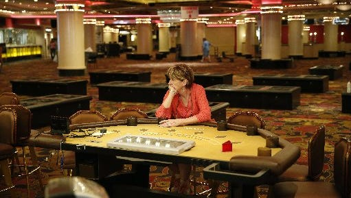 A woman who declined to give her name, sits at a table in the casino during the sale.