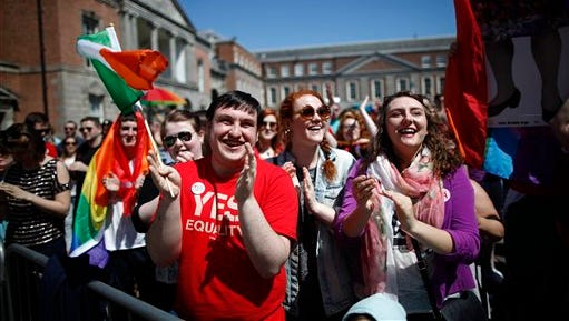 """Yes supporters celebrate as first results in the Irish referendum start to come through at Dublin castle,  Ireland, Saturday, May 23, 2015.   Ireland has voted resoundingly to legalize gay marriage in the world's first national vote on the issue, leaders on both sides of the Irish referendum declared Saturday even as official ballot counting continued. Senior figures from the """"no"""" campaign, who sought to prevent Ireland's constitution from being amended to permit same-sex marriages, say the only question is how large the """"yes"""" side's margin of victory will be from Friday's vote. (AP Photo/Peter Morrison)"""