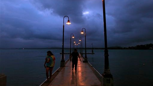 A couple walks on a pier under cloudy skies as Tropical Storm Erika approaches the island in Naguabo, Puerto Rico, on Thursday.