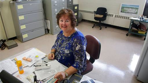 In this Wednesday, Sept. 2, 2015 photo high school nurse Kathleen Gage, instrumental in working for the accepted use of Narcan in Rhode Island schools, sits at her desk at Pilgrim High School Wednesday, Sept. 2, 2015, in Warwick, R.I. A new state law requires middle schools and high schools to stock Narcan, which can reverse the effects of an overdose of drugs such as heroin or prescription painkillers. (AP Photo/Stephan Savoia)