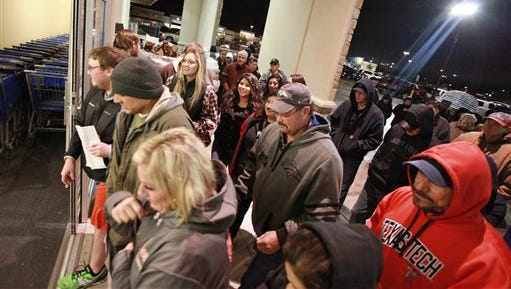 Shoppers rush through the entrance to the Academy Sports+Outdoors at 5:00 a.m. in the Chimney Rock Shopping Center on Friday, Nov. 27, 2015, in Odessa, Texas. Early numbers aren't out yet on how many shoppers headed to stores on Thanksgiving, but it's expected that more than three times the number of people will venture out to shop on the day after the holiday known as Black Friday. (Jacob Ford/Odessa American via AP) MANDATORY CREDIT