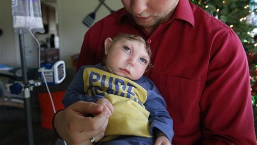 In this Tuesday, Dec. 22, 2015 photo, Brandon Buell holds his year-old son Jaxon, who was born with a rare condition that prevented much of his brain from forming and left half his skull flat, in Tavares, Fla. Brandon and his wife said presents have piled up for Jaxon, whose Christmas card with Santa became an Internet sensation.