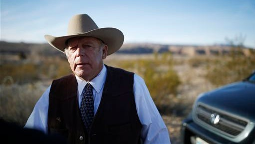 Rancher Cliven Bundy stands along the road near his ranch after speaking with media Wednesday, Jan. 27, 2016, in Bunkerville, Nev. Cliven Bundy and his wife Carol Bundy was returning from a trip to visit the family of LaVoy Finicum, a 55-year-old rancher from Cain Beds, Ariz., who died Tuesday after law enforcement officers initiated a traffic stop near the Malheur National Wildlife Refuge. It's unclear what happened in the moments before his death. (AP Photo/John Locher)