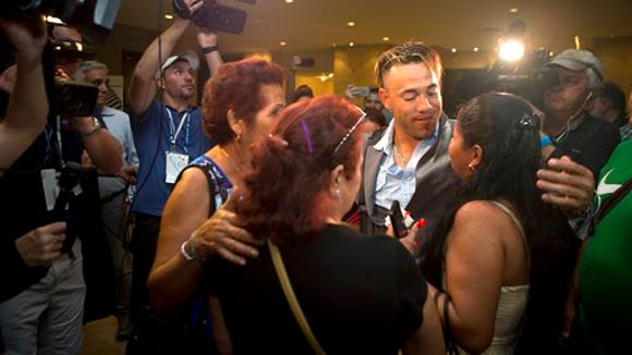 Tampa Bay Rays outfielder Dayron Varona,  of Cuba,  center right, is greeted by members of his family living in Havana who haven't seen him in three years, as he arrives at the team hotel in Havana, Cuba, Sunday, March 20, 2016. The Rays will play a game against Cuba's national team on March 22.(AP Photo/Rebecca Blackwell)