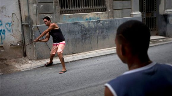 Young baseball players practice their skills with sticks and bottle caps in Old Havana, Cuba, Saturday, March 19, 2016. President Barack Obama will visit the island on March 20. During his three-day trip, the first to the country by a sitting U.S. president in nearly 90 years, he will meet with President Raul Castro at the Palace of the Revolution and attend an exhibition baseball game. (AP Photo/Rebecca Blackwell)