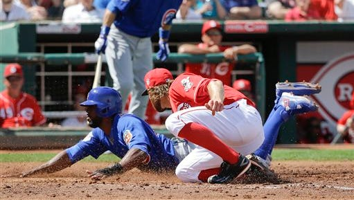 Dexter Fowler scores on a wild pitch by Reds left-hander Tony Cingrani.