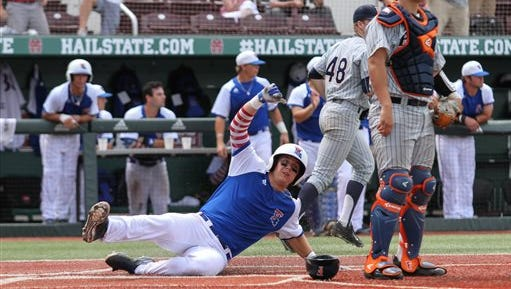 Louisiana Tech's Jordan Washam slides home as Cal State Fullerton catcher Chris Hudgins looks on during the fifth inning of their NCAA college baseball regional tournament game at Dudy Noble Field in Starkville, Miss., Sunday, June 5, 2016. (James Pugh/The Laurel Chronicle via AP)