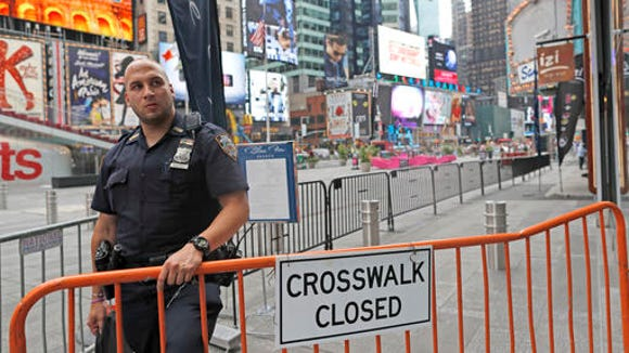 A police officer stands guard at a section of Times Square closed off to pedestrians after the bombing in the Chelsea neighborhood, Sunday, Sept. 18, 2016, in New York.