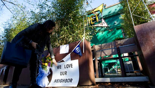"""Meighan Stone places a support banner with flowers outside the door of Comet Ping Pong pizza shop, in Washington, Monday. A fake news story prompted a man to fire a rifle inside a popular Washington, D.C., pizza place as he attempted to """"self-investigate"""" a conspiracy theory that Hillary Clinton was running a child sex ring from there, police said.  ( AP Photo/Jose Luis Magana)"""