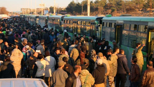 This image released on Thursday, Dec. 15, 2016 by Aleppo 24, shows residents gathered near green government buses for evacuation from eastern Aleppo, Syria. The evacuation of eastern Aleppo stalled Friday after an eruption of gunfire, as the Syrian government and rebels threw accusations at each other, raising fears that a peaceful surrender of the opposition enclave could fall apart with thousands of people believed to be still inside.
