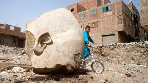 A boy rides his his bicycle past a recently discovered statue in a Cairo slum that may be of pharaoh Ramses II, in Cairo, Egypt, Friday, March 10, 2017. Archeologists in Egypt have discovered a massive statue that may be of pharaoh Ramses II, one of the country's most famous ancient rulers. The colossus, whose head was pulled from mud and groundwater by a bulldozer on Thursday, is around eight meters (yards) tall and was discovered by a German-Egyptian team.