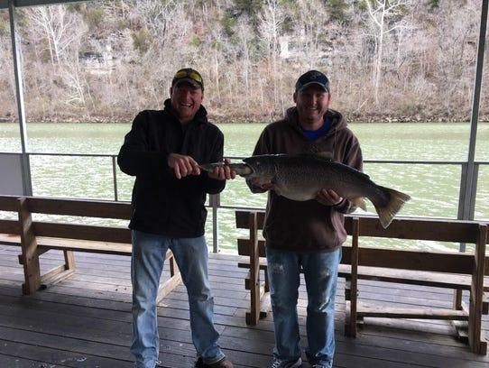 Stephen Adam, left, stuffs a rainbow trout into the