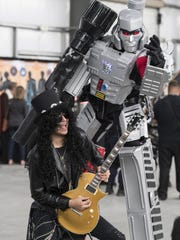 """Rafael R. Salazar of Fresno as """"Slash"""" from Guns and Roses poses for pictures with Megatron during the Tulare Sci-Fi Con at the International Agri-Center on Saturday, March 11, 2017."""