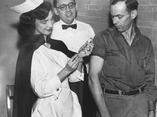 """In a photo published Jan. 11, 1957, nurse Wanda Cooper administers a Salk anti-polio vaccine shot to employee Joe Plummer at Spinlab's 312 West Vine Avenue plant. Spinlab President Hugh Neil is at center. According to the story: """"The nurse who helped give the shots, pretty red-headed Wanda Cooper, a recent bride, is herself recovering from a polio attack of two years ago."""""""