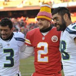 Seattle quarterback Russell Wilson (left), Kansas City punter Dustin Colquitt and tight end Tony Moeaki pose for a photo after a November game at Arrowhead Stadium. Moeaki, a one-time Iowa star at tight end, formerly played for the Chiefs and is now a member of the NFC champion Seahawks.