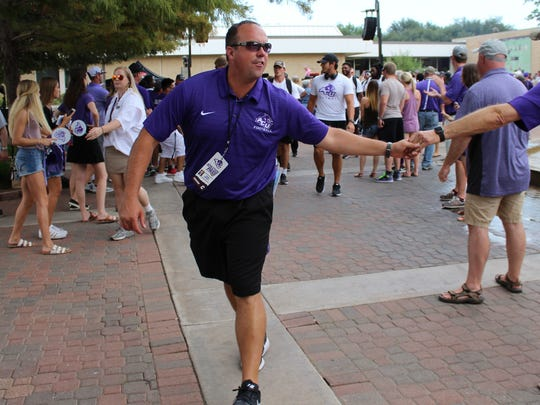 Wildcats head coach Adam Dorrel slaps a fan's hand while leading his team on the first Wildcat Walk through the center of the Abilene Christian University campus.