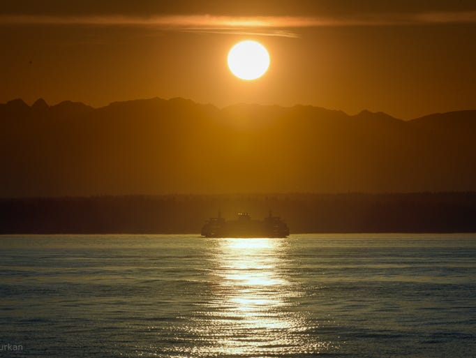 A ferryboat cruises through  Seattle, Wash., during