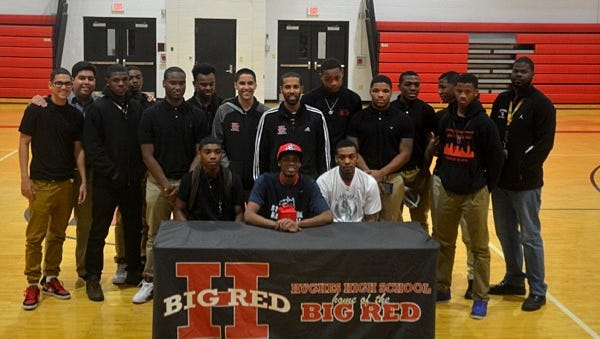 Corry Long (center/seated) appears with members of the Hughes basketball team on National Signing Day, Nov. 9.