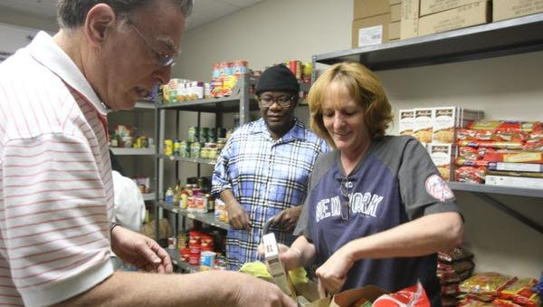 Jude Jean Pierre, center, of Spring Valley watches as volunteers Bobbi Curti and Harvey Gultz packs food from the food pantry at Rockland Independent Living Center in New City May 6, 2014.