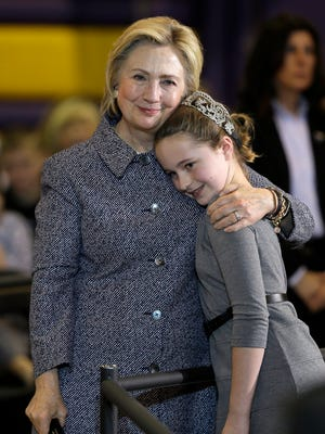 Democratic presidential candidate Hillary Clinton gets a hug from fifth-grader Hannah Tandy during a town hall meeting at Keota High School, Tuesday, Dec. 22, 2015, in Keota.