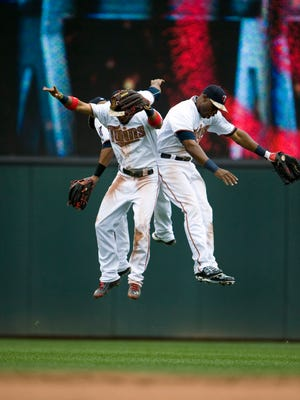 Twins left fielder Eddie Rosario (20) (L) and center fielder Aaron Hicks (32) (back) and right fielder Torii Hunter (48) (R) celebrate a win over the Red Sox.