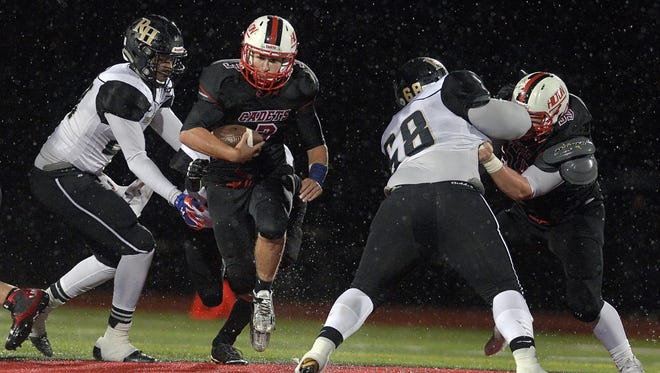 Hilton's Dillon Philmon, center, breaks through a hole in the line of scrimmage against Rush-Henrietta at Hilton High School on Oct. 16, 2015.