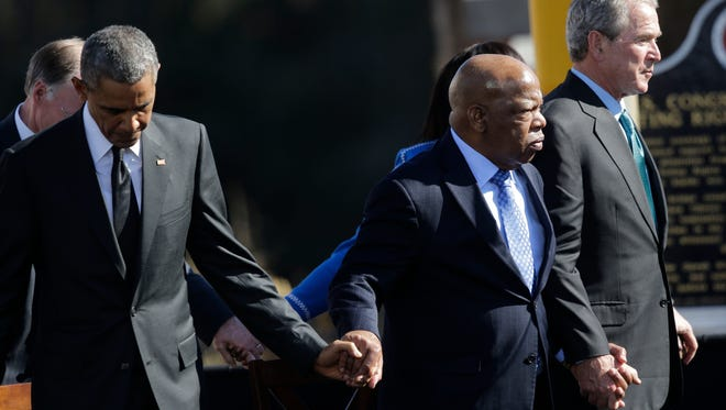 President Barack Obama, left, U.S. Rep. John Lewis, D-Ga., and Former President George W. Bush hold hands for a prayer after Obama spoke near the Edmund Pettus Bridge.