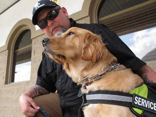 Army veteran Joe Aguirre drapes an arm across the back of his service dog, Munger, in Fayetteville, N.C. The Department of Veterans Affairs is in the middle of a multi-year study to determine whether it should pay for such psychiatric service dogs.