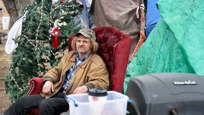 In this Dec. 12, 2017, photo, a man sits by his tent at a homeless camps in Colorado Springs, Colo. (Jerilee Bennett/The Gazette via AP)