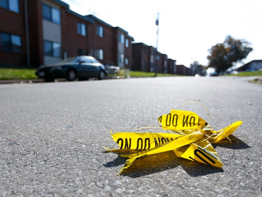 The remnants of crime scene tape sit in the road on