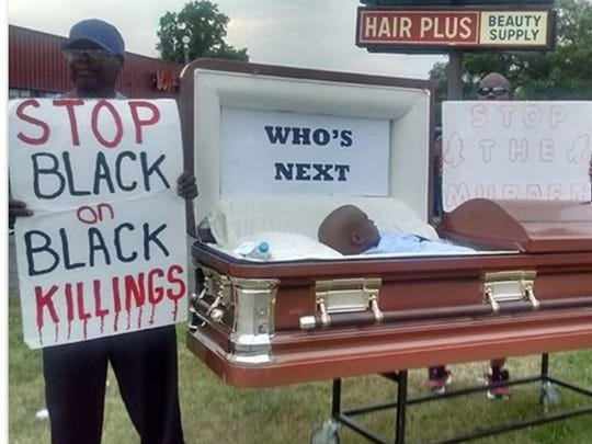 Rev. Anthony Pippens Sr. of Greater New Hope church on Indianapolis' Northwestwide holds a sign next to a coffin with a mannequin inside that he rolls through neighborhoods to bring attention to the city's violence.