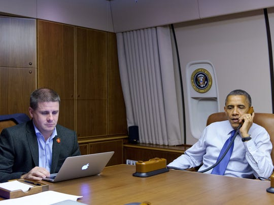 President Barack Obama speaks on the phone to national volunteer leaders in battleground states from Air Force One while travelling from Denver to Los Angeles on October 24, 2012. At left is then-White House Communications Director Dan Pfeiffer.