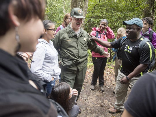 Blue Ridge Parkway Superintendent Mark Woods, left, and superintendent of the Great Smokies Cassius Cash, right, share a laugh with Cherokee middle students while stopping to name a snail April 22, 2016 while on a hike through the Deep Creek section of the Great Smokies.